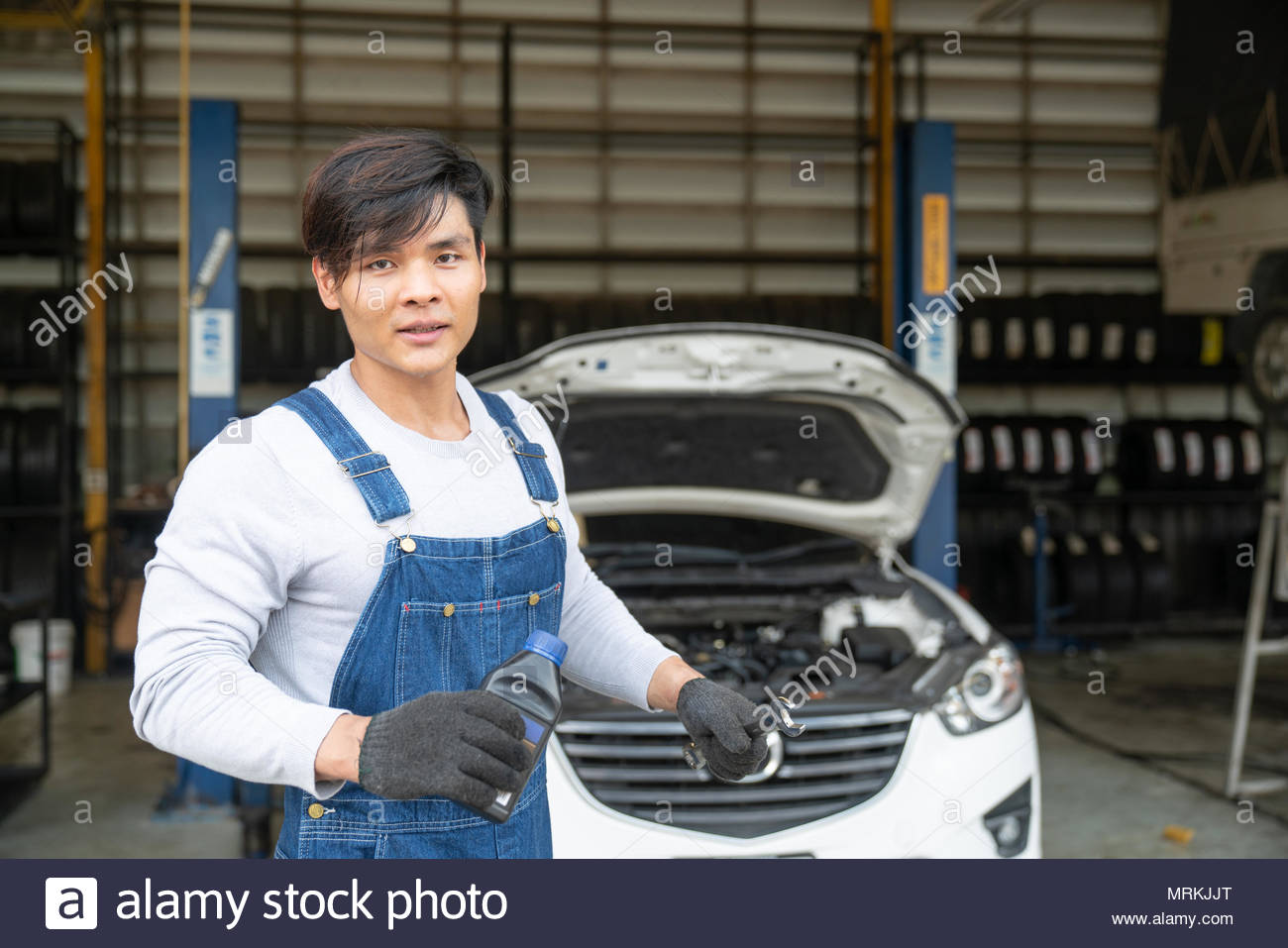 car mechanic with wrench in garage. - Stock Image