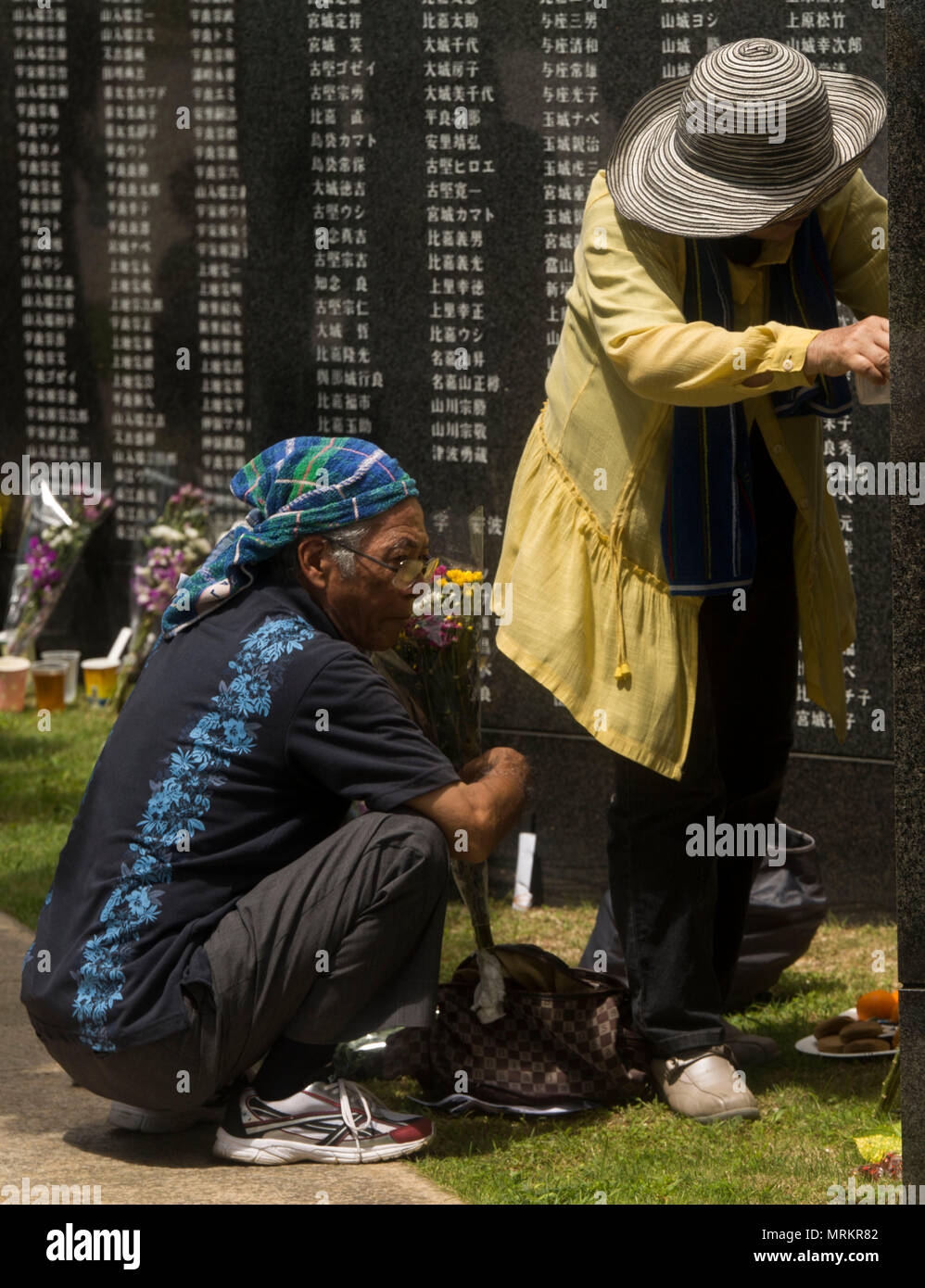 Okinawan residents place flowers and pray at the Cornerstone of Peace memorial wall during the 2017 Okinawa Memorial Day service June 23, 2017 at Peace Memorial Park, Itoman, Japan. The ceremony brought together service members and Okinawan residents to honor all who lost their lives in the Battle of Okinawa. The memorial walls are inscribed with over 240,000 names of people who died, regardless of nationality, civilian or military status in the battle. During the ceremony all who attended stood for a moment of silence honoring those who gave the ultimate sacrifice for their country. (U.S. Mar Stock Photo