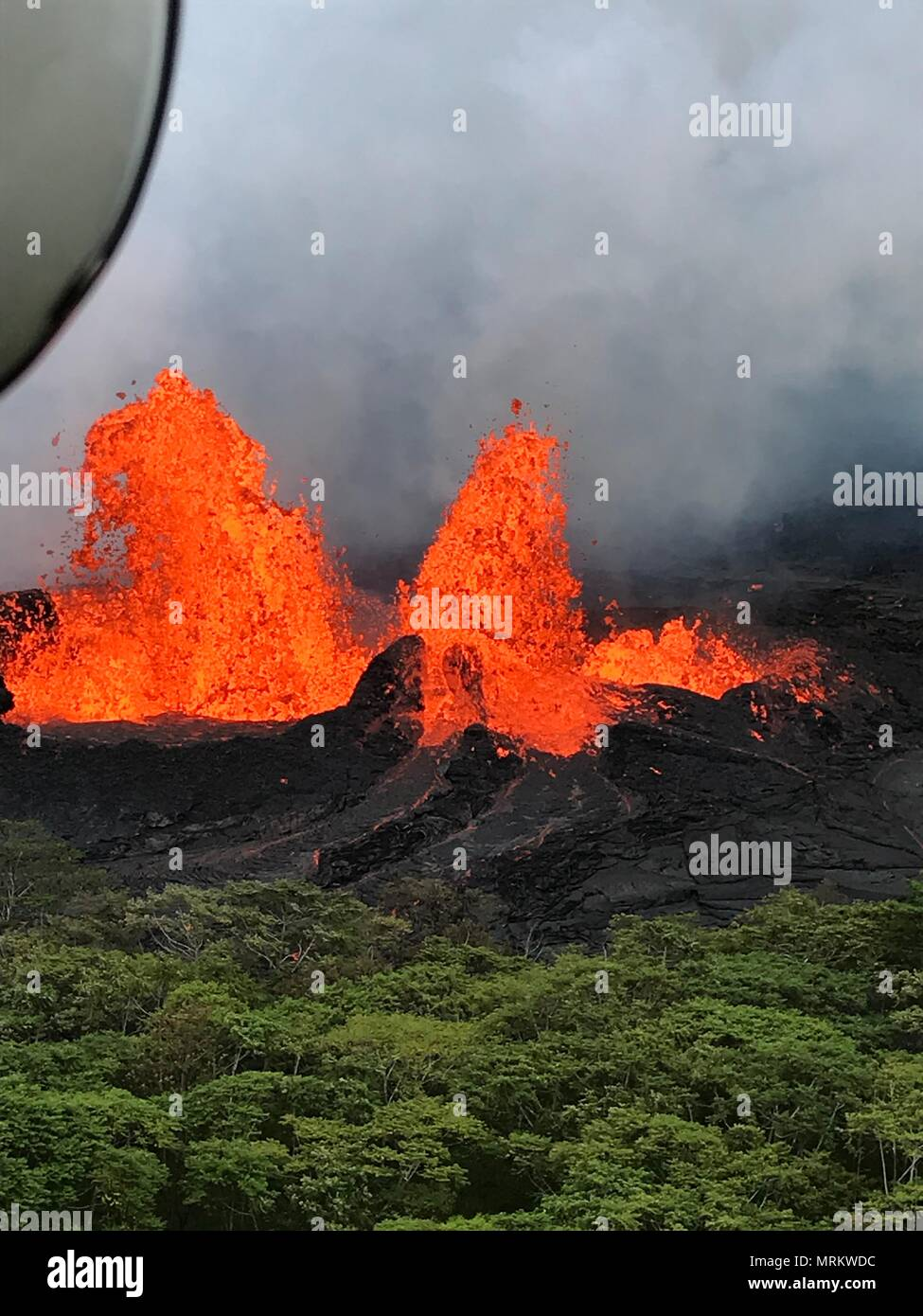 Molten lava spews hundreds of feet into the air at fissure 22 from the eruption of the Kilauea volcano May 21, 2018 in Pahoa, Hawaii.Stock Photo