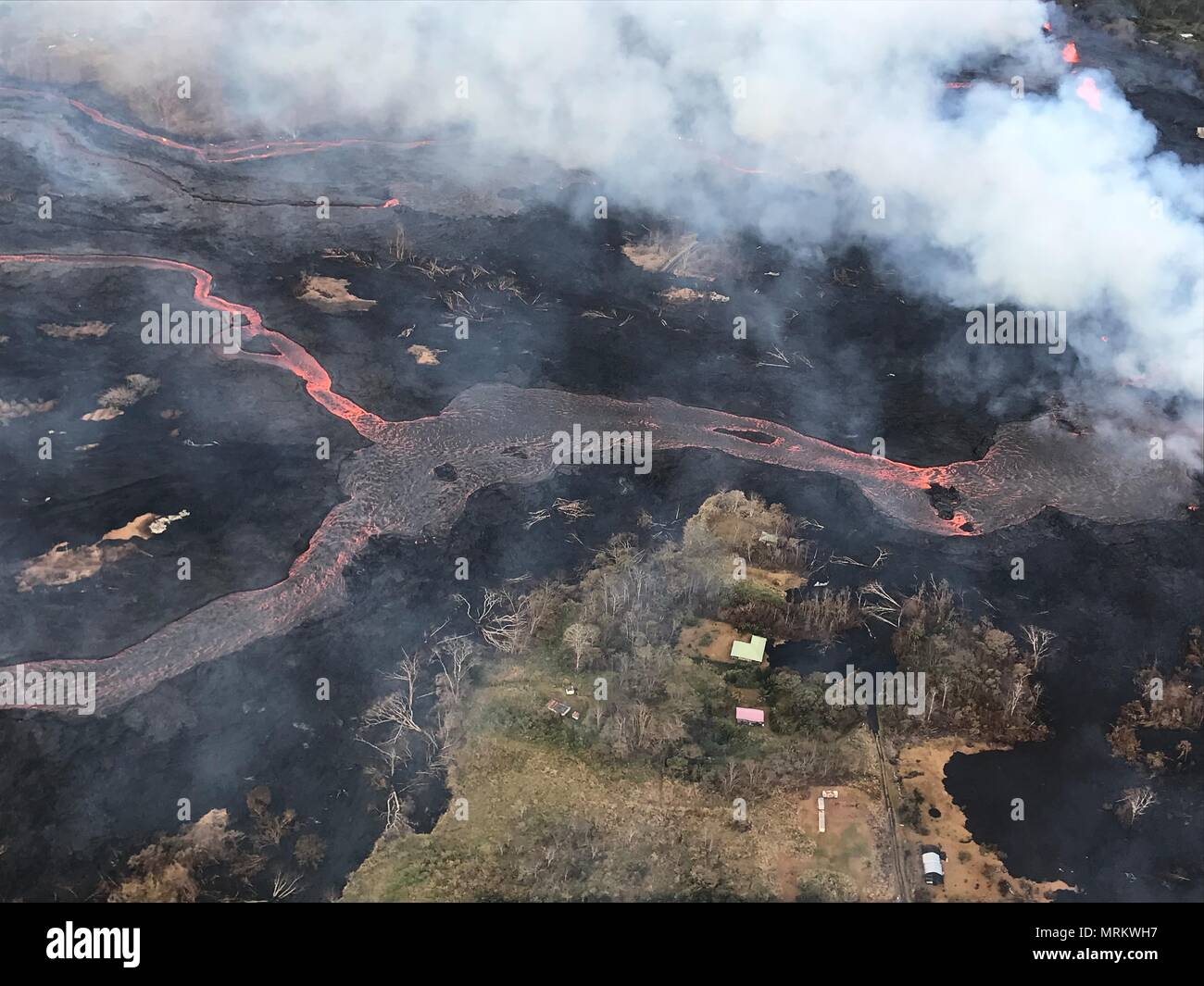 Channelized lava streams down fissure 22 in the East Rift Zone from the eruption of the Kilauea volcano May 23, 2018 in Pahoa, Hawaii.Stock Photo