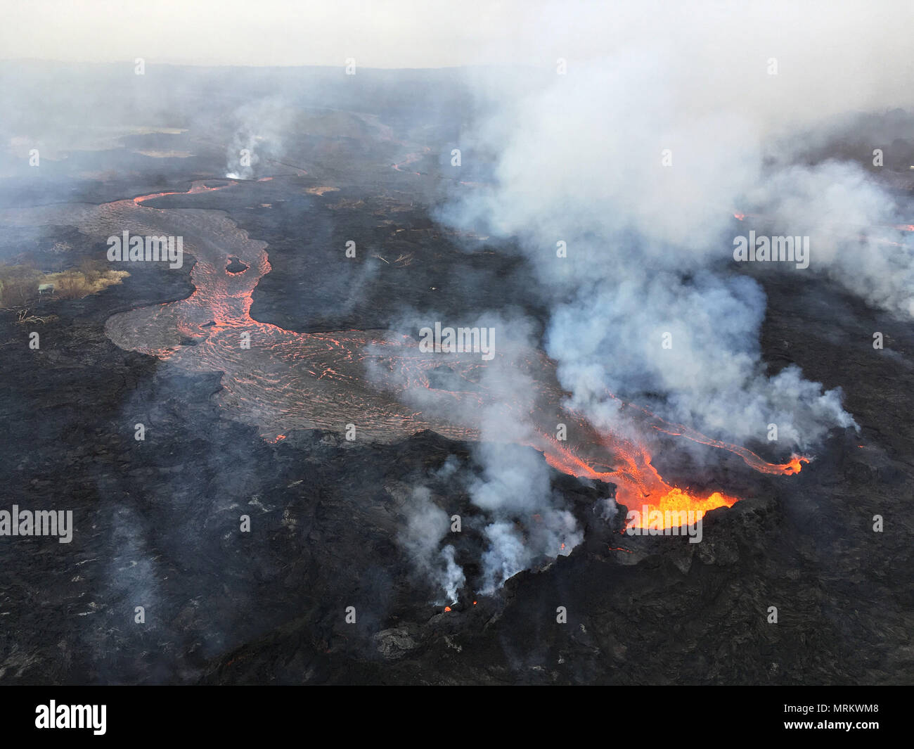 Channelized lava streams down fissure 22 in the East Rift Zone from the eruption of the Kilauea volcano May 24, 2018 in Pahoa, Hawaii. Stock Photo