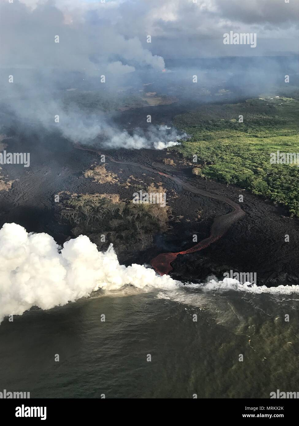 Lava and poisonous sulfur dioxide plumes rise as molten magma reaches the ocean from the eruption of the Kilauea volcano May 23, 2018 in Pahoa, Hawaii. Hot lava entering the ocean creates a dense white plume called 'laze' (short for 'lava haze'). Laze is formed as hot lava boils seawater to dryness. The process leads to a series of chemical reactions that create a billowing white cloud composed of a condensed seawater steam, hydrochloric acid gas, and tiny shards of volcanic glass. The cloud is as corrosive as dilute battery acid, and should be avoided. - Stock Image