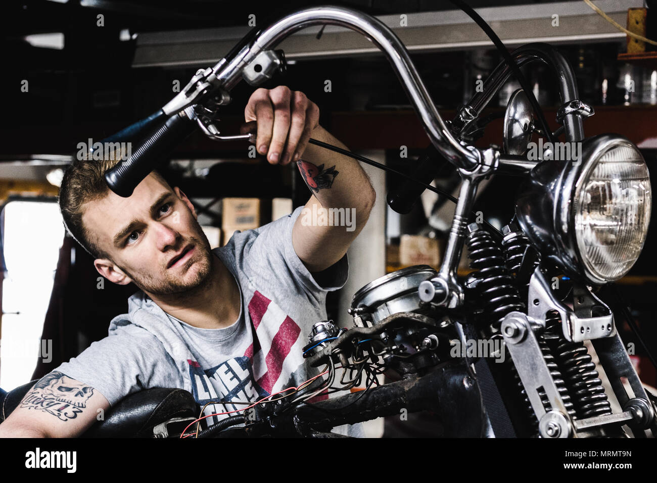 A mechanic working on his motorcycle - Stock Image