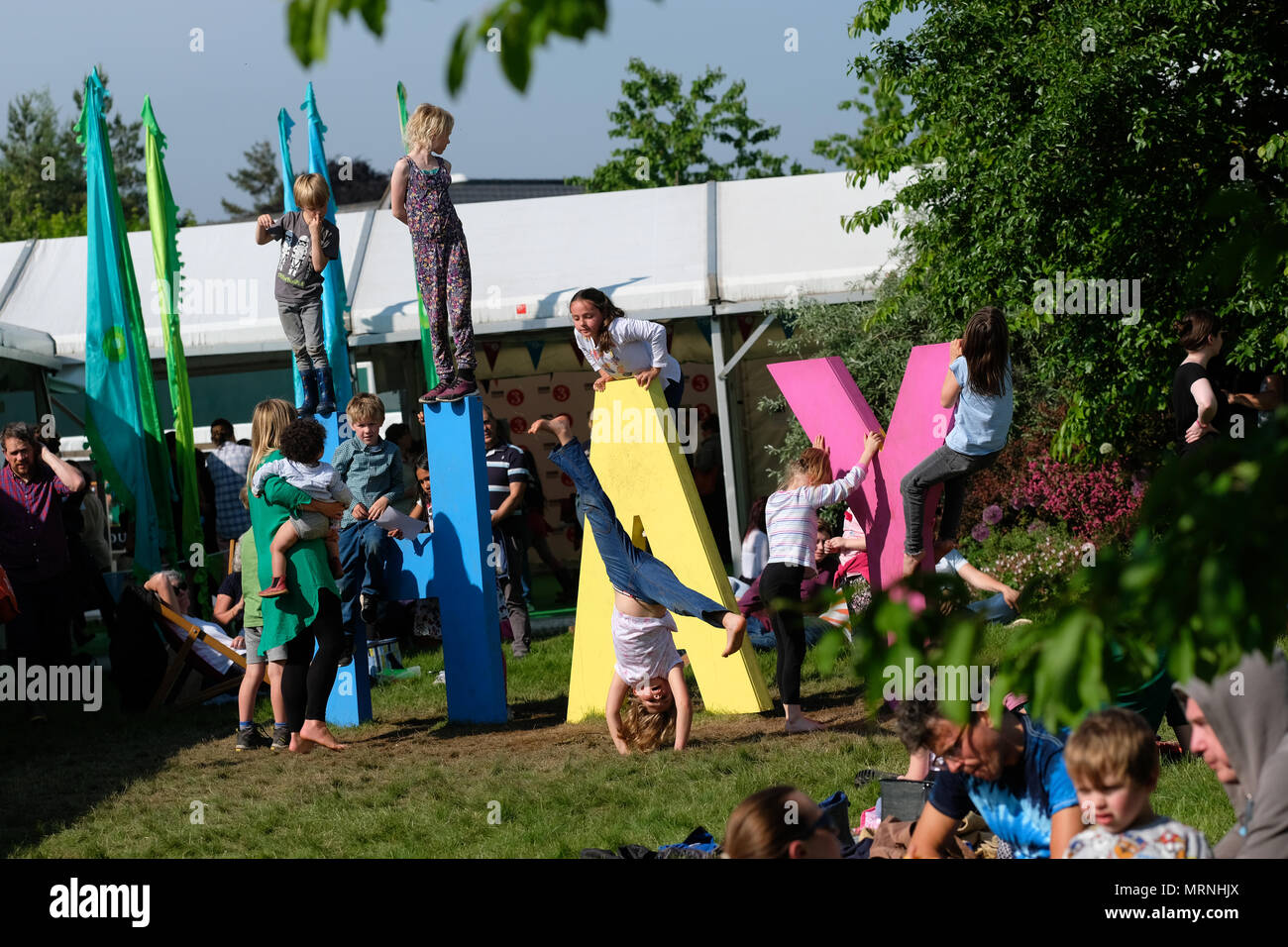 Hay Festival, Hay on Wye, UK - May 2018 - Children play on the giant HAY letters on the Festival lawn as the late afternoon sun shines on Hay - Photo Steven May / Alamy Live News - Stock Image