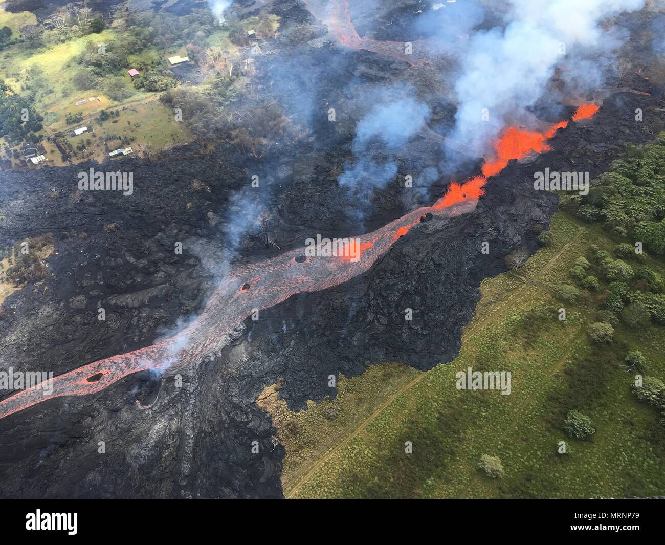 Channelized lava streams down fissure 20 in the East Rift Zone from the eruption of the Kilauea volcano May 19, 2018 in Pahoa, Hawaii. Stock Photo
