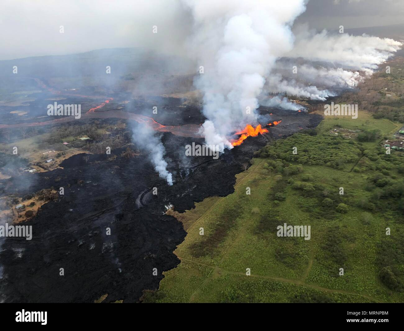 Channelized lava streams down fissure 22 in the East Rift Zone from the eruption of the Kilauea volcano May 21, 2018 in Pahoa, Hawaii. Stock Photo