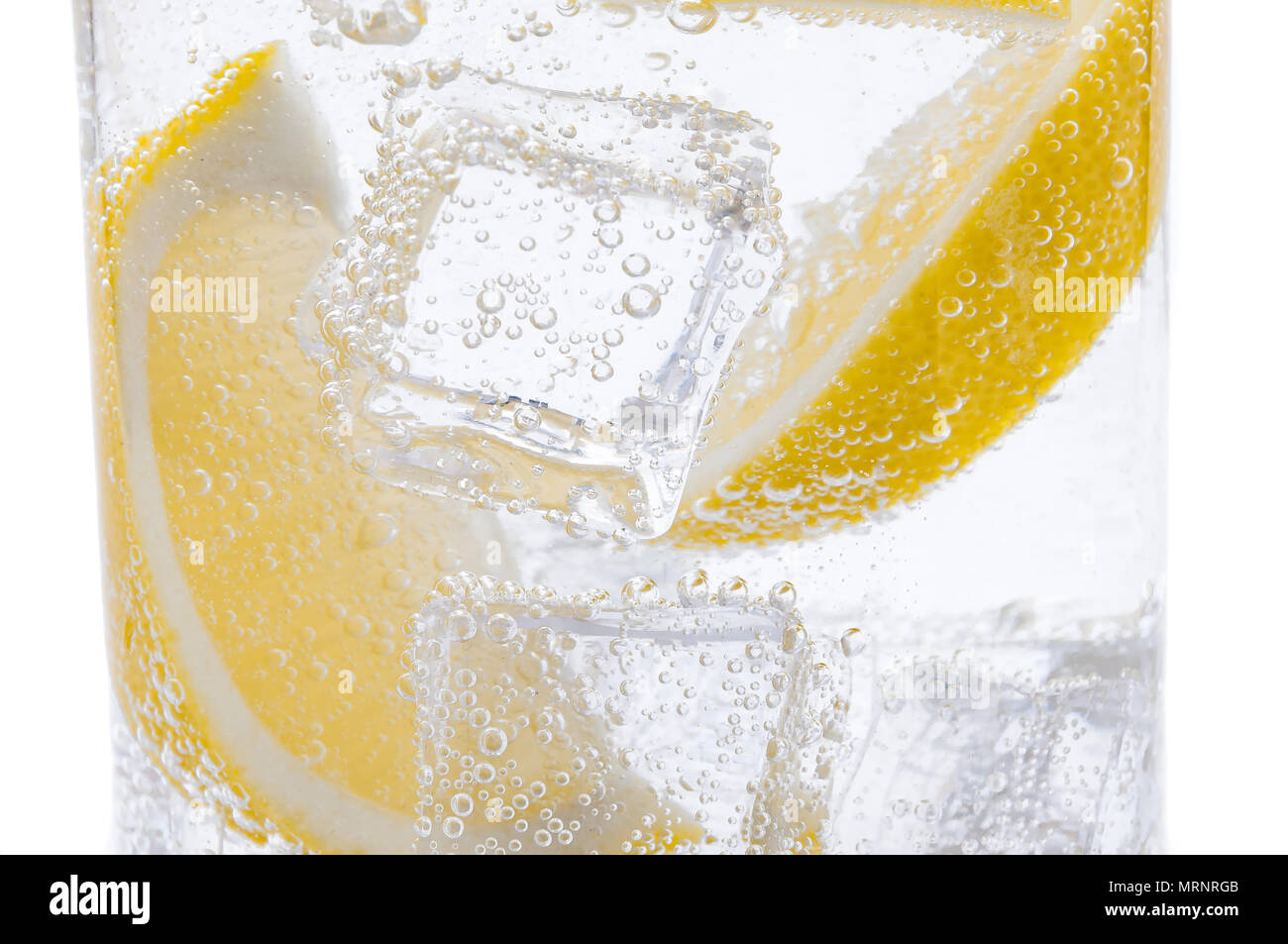 Slices of fresh juicy yellow lemon with ice in water. - Stock Image