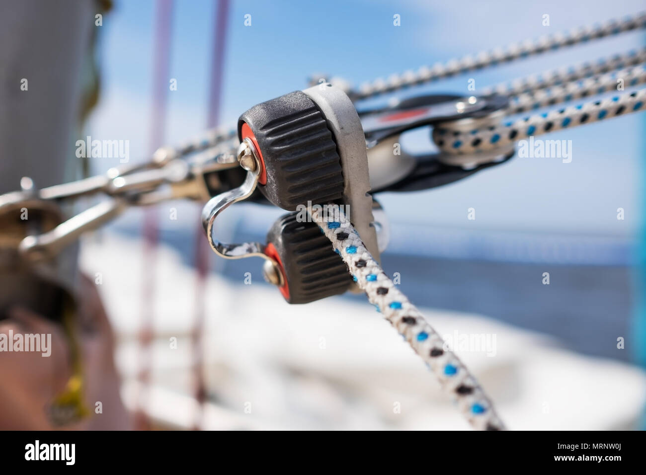close up on winch and rope of yacht over blue sea - Stock Image