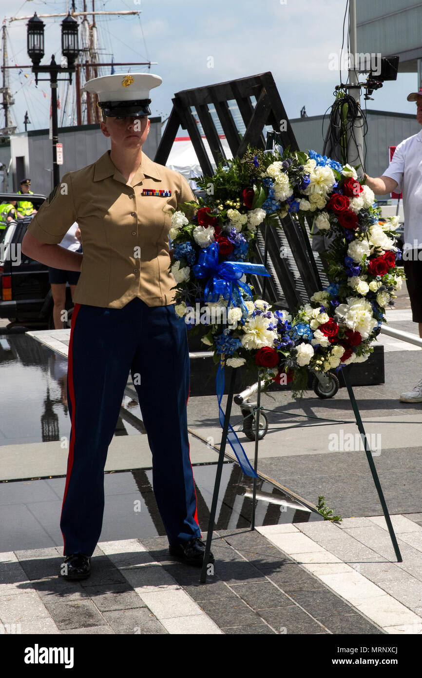 Sgt. Julia Junk represents the Marine Corps during the Fallen Warriors Memorial Ceremony in Boston, Mass., June 18, 2017.  During the ceremony, representatives with the U.S. Navy and U.S. Marine Corps, as well as Naval forces from around the world, laid five wreaths to honor their fallen comrades. In addition, seven yellow roses were laid at the memorial to pay tribute to the seven sailors who lost their lives aboard the USS Fitzgerald earlier this week. Junk is a field radio operator with Marine Wing Communications Squadron 28, Marine Aircraft Group 14, 2nd Marine Aircraft Wing. (U.S. Marine  Stock Photo