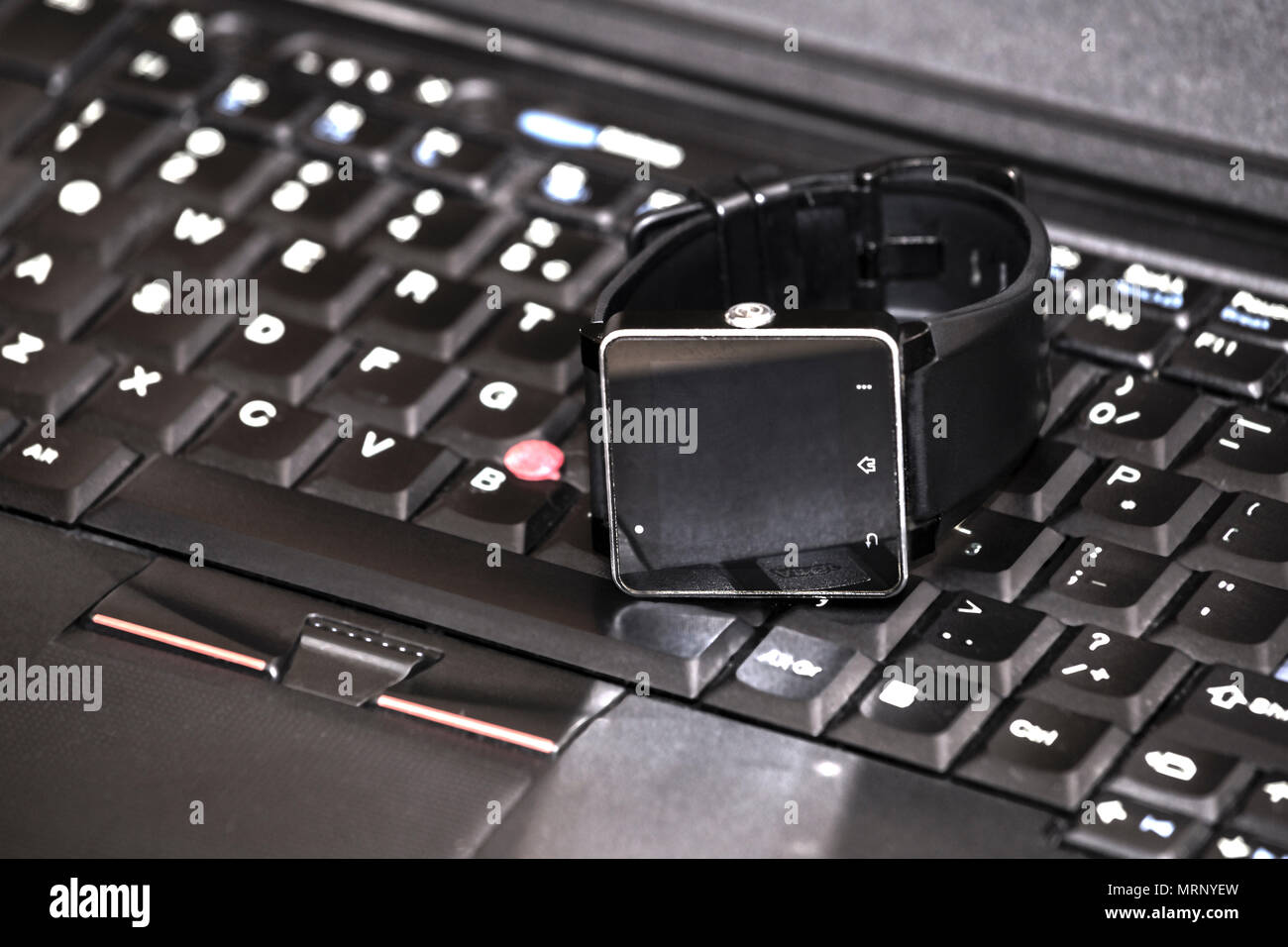 Smart wrist watch laying on a laptop keyboard. Abstract: always stay connected to internet and media. - Stock Image