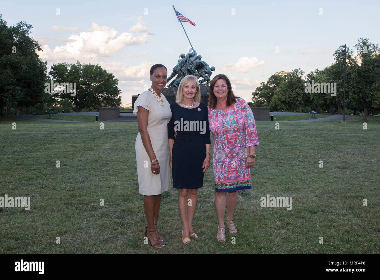 From left, Ladonna Crenshaw, Bonnie Perdue and Suzanne Dana pose for during a sunset parade at the Marine Corps War Memorial, Arlington, Va., June 27, 2017. Sunset parades are held as a means of honoring senior officials, distinguished citizens and supporters of the Marine Corps. (U.S. Marine Corps photo by Cpl. Christian Varney) - Stock Image