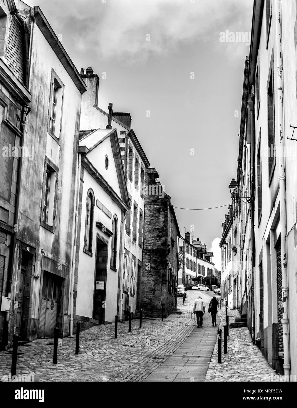 Two People Walking Up One Of The Steeper Historic Streets In Quimper Brittany France
