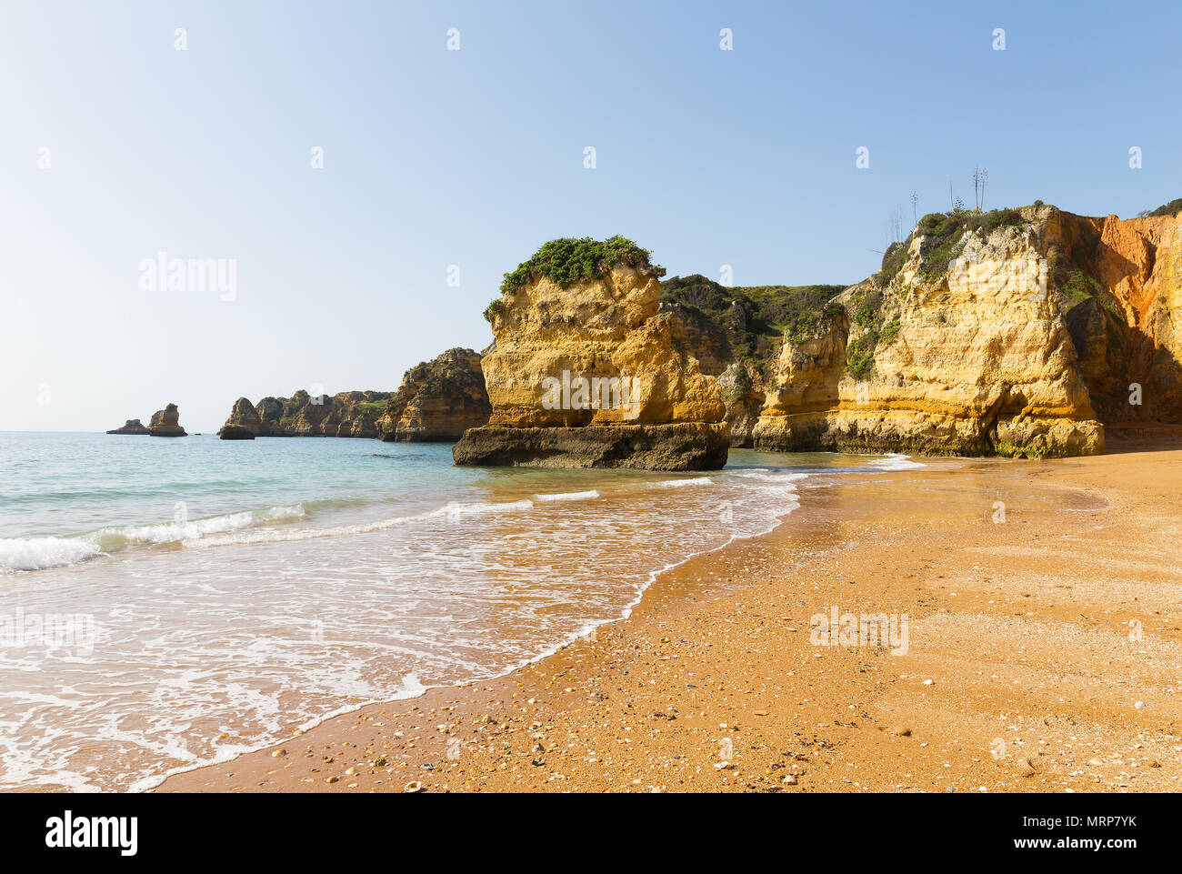Atlantic sandy beach at sunrise with seashells left by the tide. Waves are rolling among the cliffs under the morning sun in Lagos, Portugal. Stock Photo