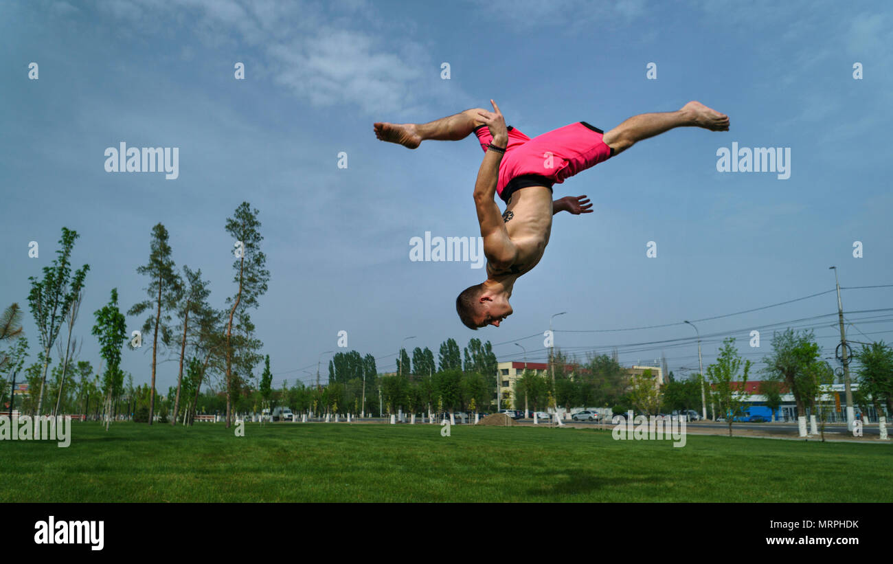 Tricking on lawn in park. Man flips back and kick. Martial arts and parkour. Street workout. - Stock Image