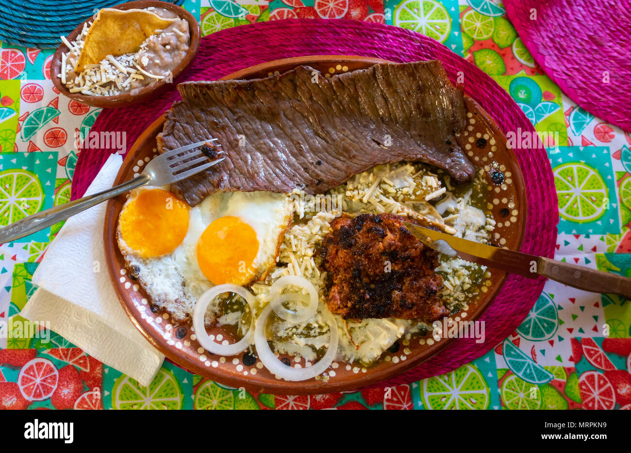 A full Mexican breakfast, with steak, sausage, eggs, beans, cheese, tortillas and a green sauce. - Stock Image