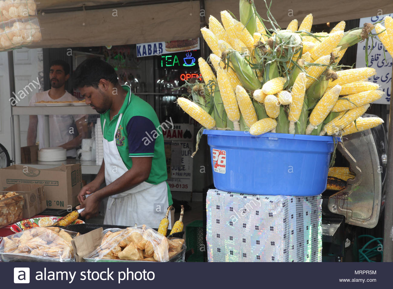 An Indian applies chili powder and other spices to barbecued corn-on-the-cob at Little India in Toronto, Ontario, Canada. Stock Photo