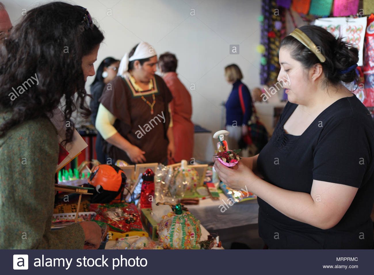 A woman selling a skeleton figure on the Day of the Dead. The Day of the Dead celebrations in Mexico is among the most important traditional religious - Stock Image