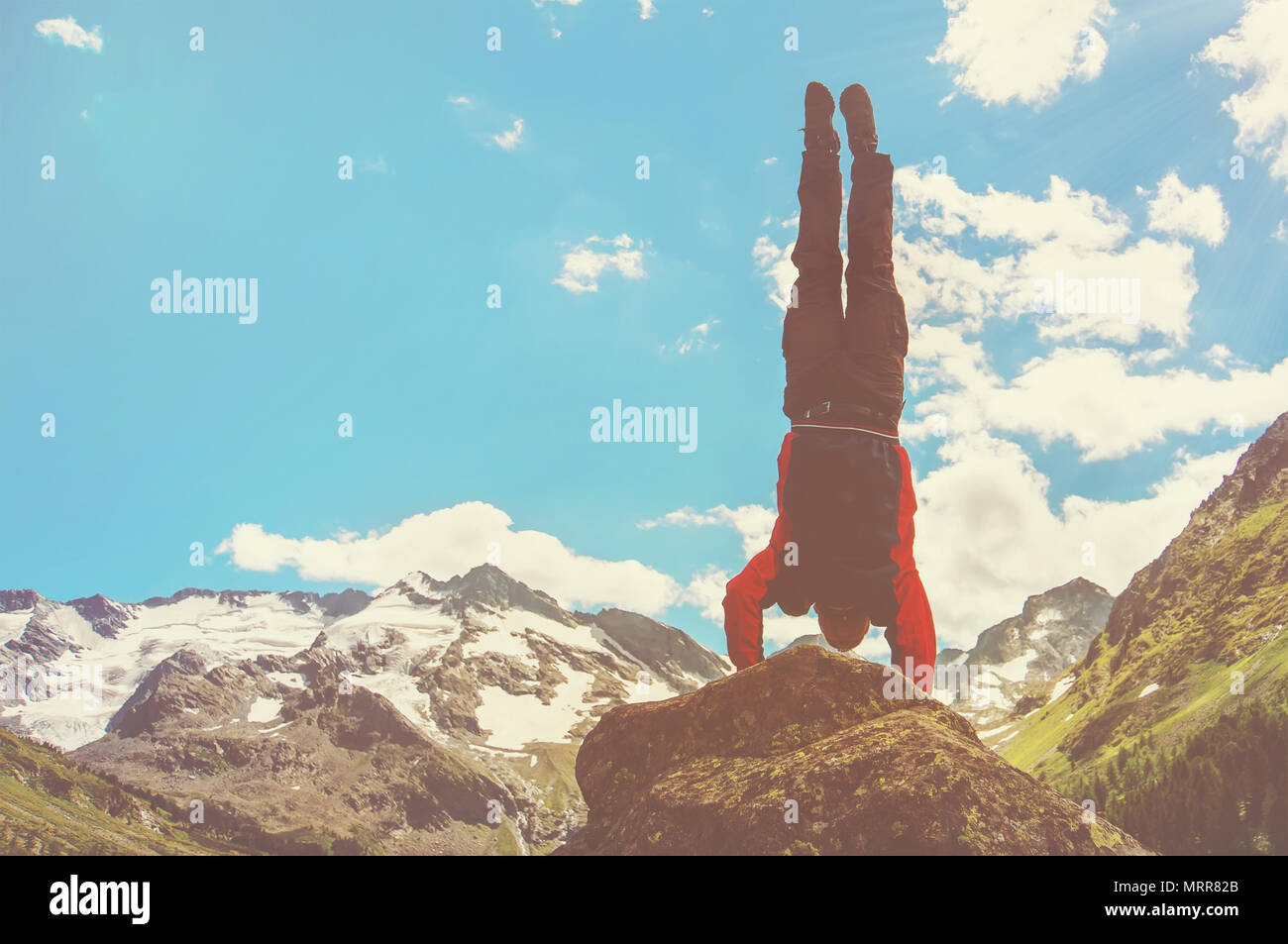 Practice gymnastic exercises in the open air in nature. Stuntman doing a dangerous trick on the edge of a precipice high in the mountains, handstand.  - Stock Image