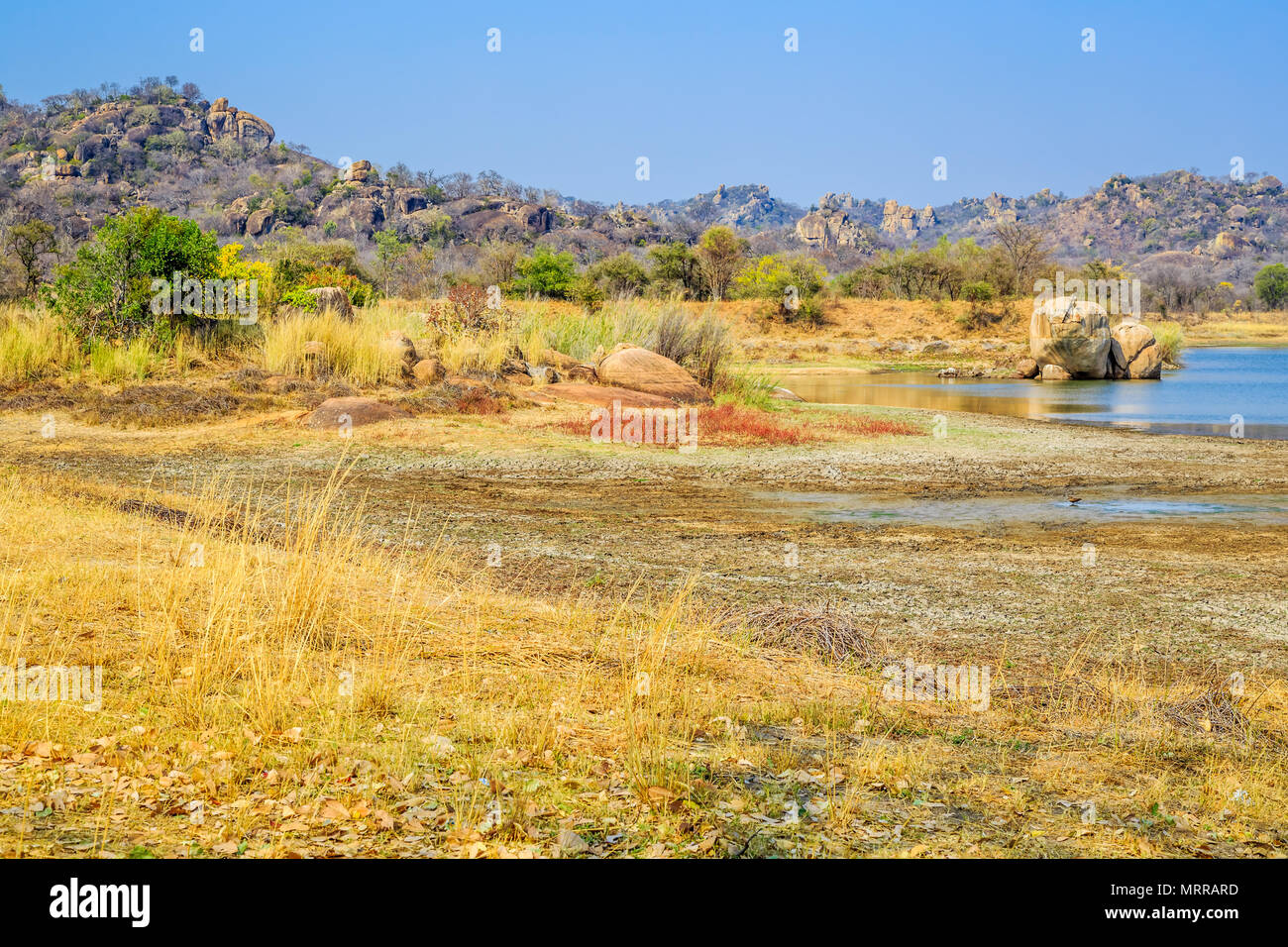 View of a lake surrounded by rocks, in Matobo National Park, Zimbabwe. September 26, 2016. - Stock Image