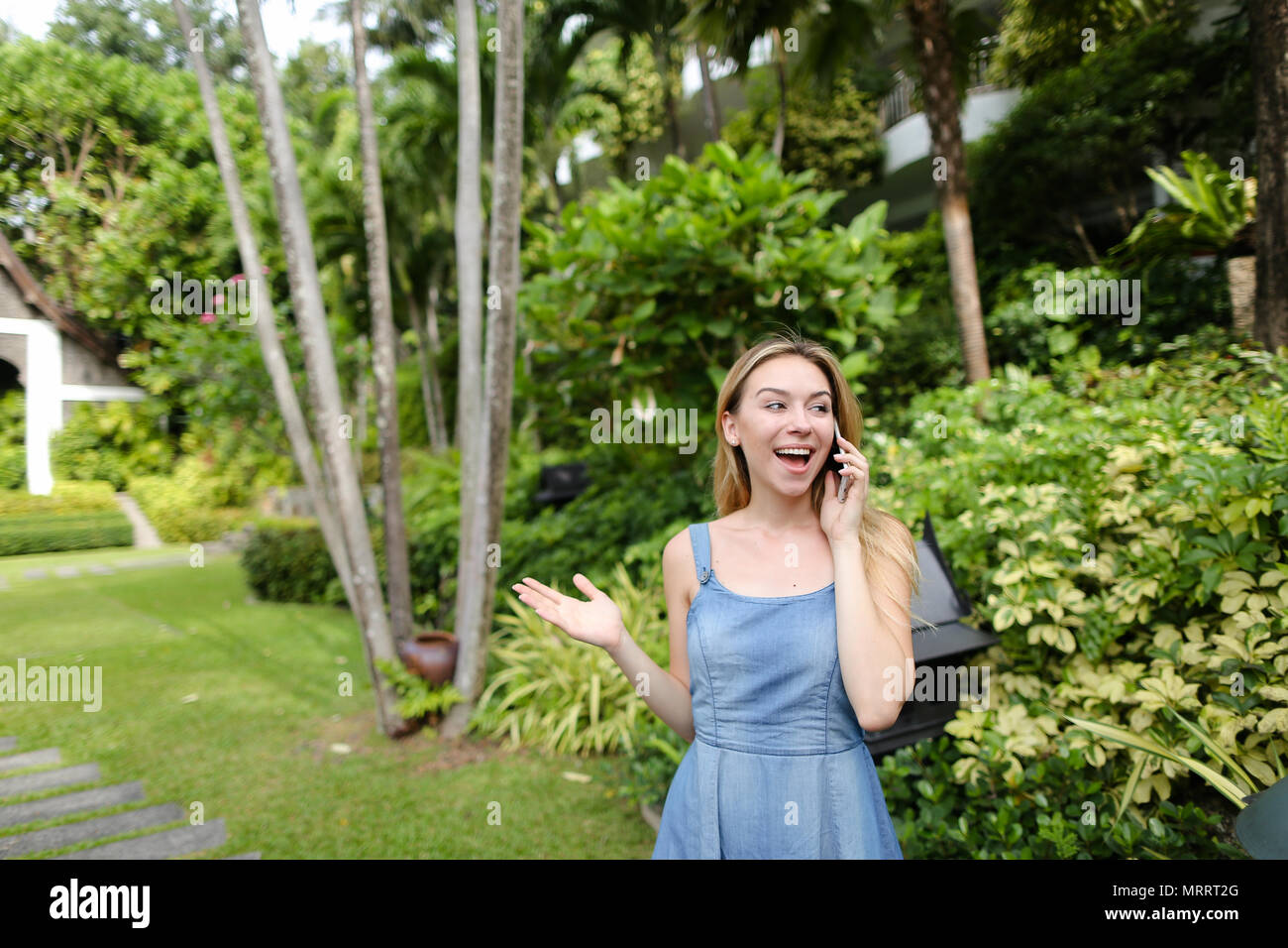 Young woman talking by smartphone in garden near trees, wearing jeans sundress. - Stock Image