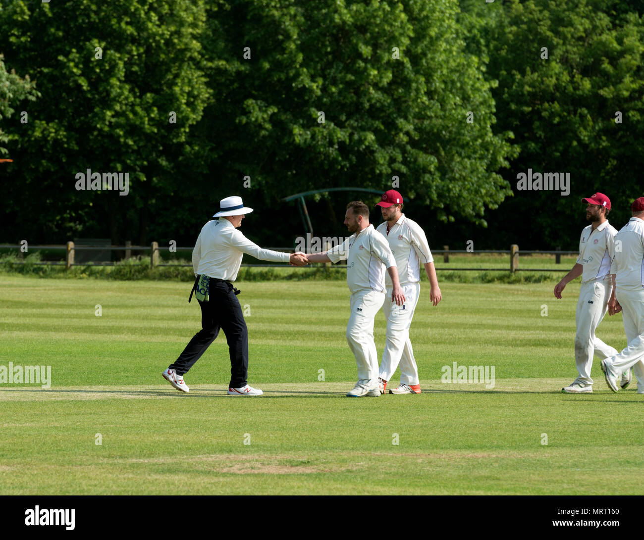 Village cricket at Wellesbourne, Warwickshire, England, UK. Player shaking hands with an umpire after the match. Stock Photo