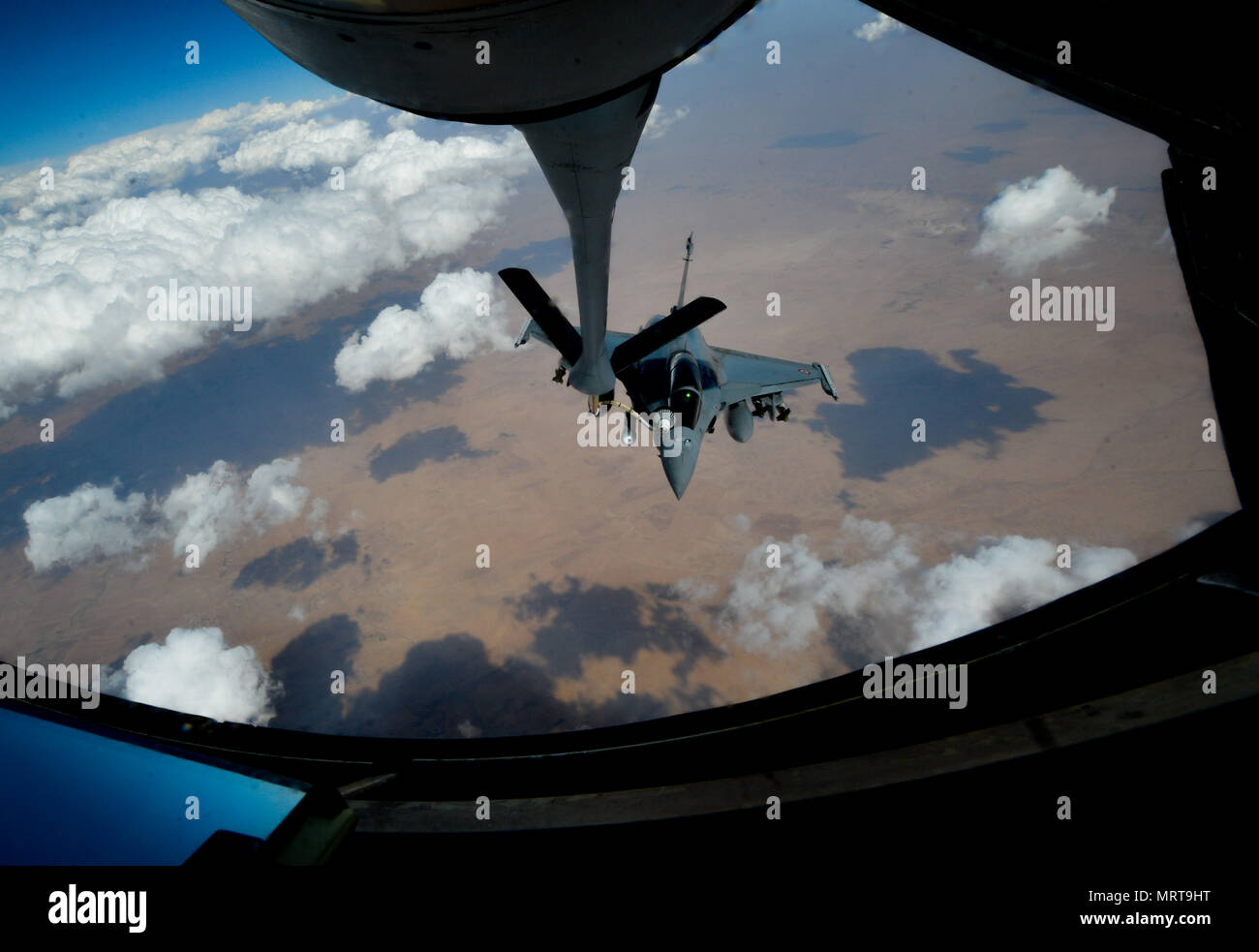 A French air force Rafale receives fuel from a 340th Expeditionary Air Refueling Squadron KC-135 Stratotanker in support of Operation Inherent Resolve, July 1, 2017.Rafale is a French twin-engine, canard delta wing, multirole fighter aircraft with a wide range of weapons. The Rafale is intended to perform air supremacy, interdiction, aerial reconnaissance, ground support, in-depth strike and anti-ship strike missions. (U.S. Air Force photo by Staff Sgt. Michael Battles) - Stock Image
