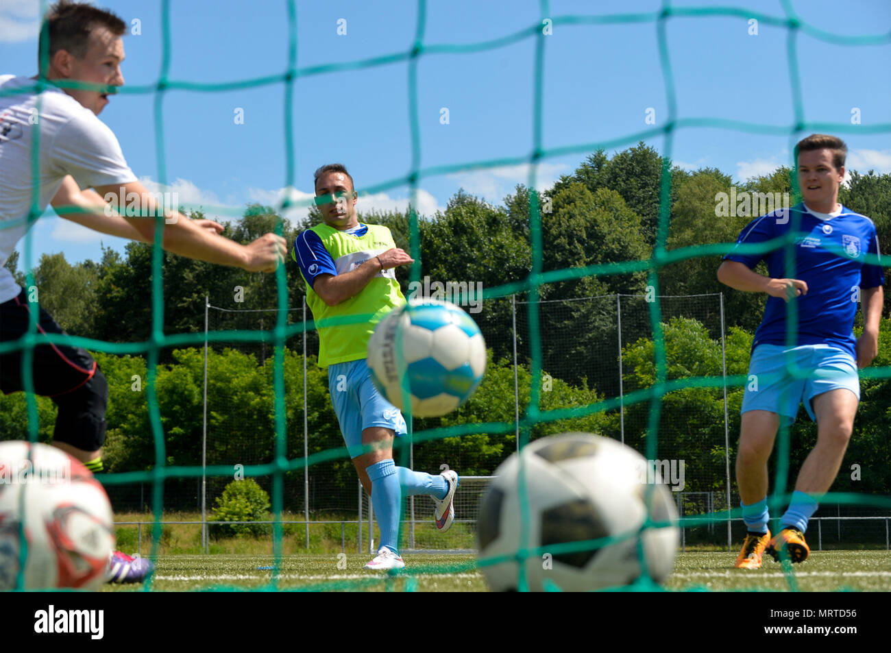 Ramstein Air Base Airmen and Fussballverein Ramstein Fußball Club A-Team play a game of soccer during the Grassroots program sports day, at FV Olympia Field in Ramstein Misenbach, Germany, June 24, 2017. The Grassroots program aims to involve Airmen socially in the local community, forge friendships and raise awareness of German culture and general understanding. (U.S. Air Force photo by Staff Sgt. Nesha Humes) - Stock Image