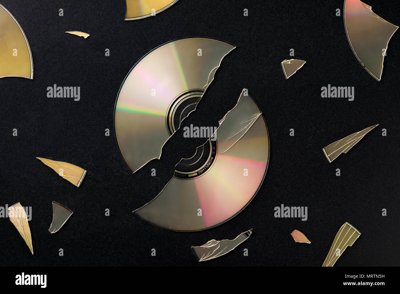 Broken Compact Disc with Pieces Scattared on Black Surface - Stock Image
