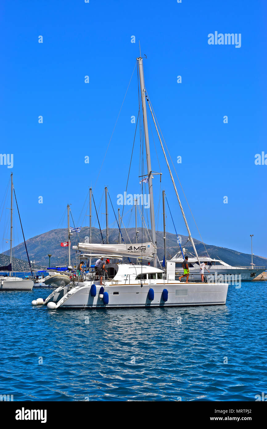 A modern catamaran departs Sami harbour on the Greek island of Cephalonia or Kefalonia on a sunny day with clear blue skies and sea - Stock Image