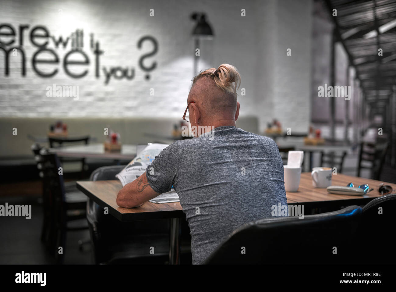 Man sporting shaven head and tied up ponytail hairstyle Stock Photo