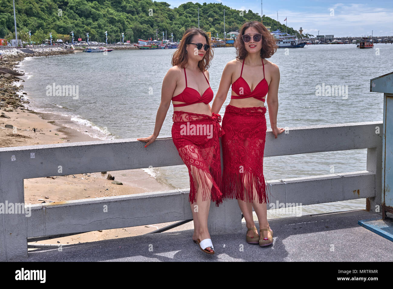 Two women dressed alike in red dresses. Thailand Southeast Asia - Stock Image