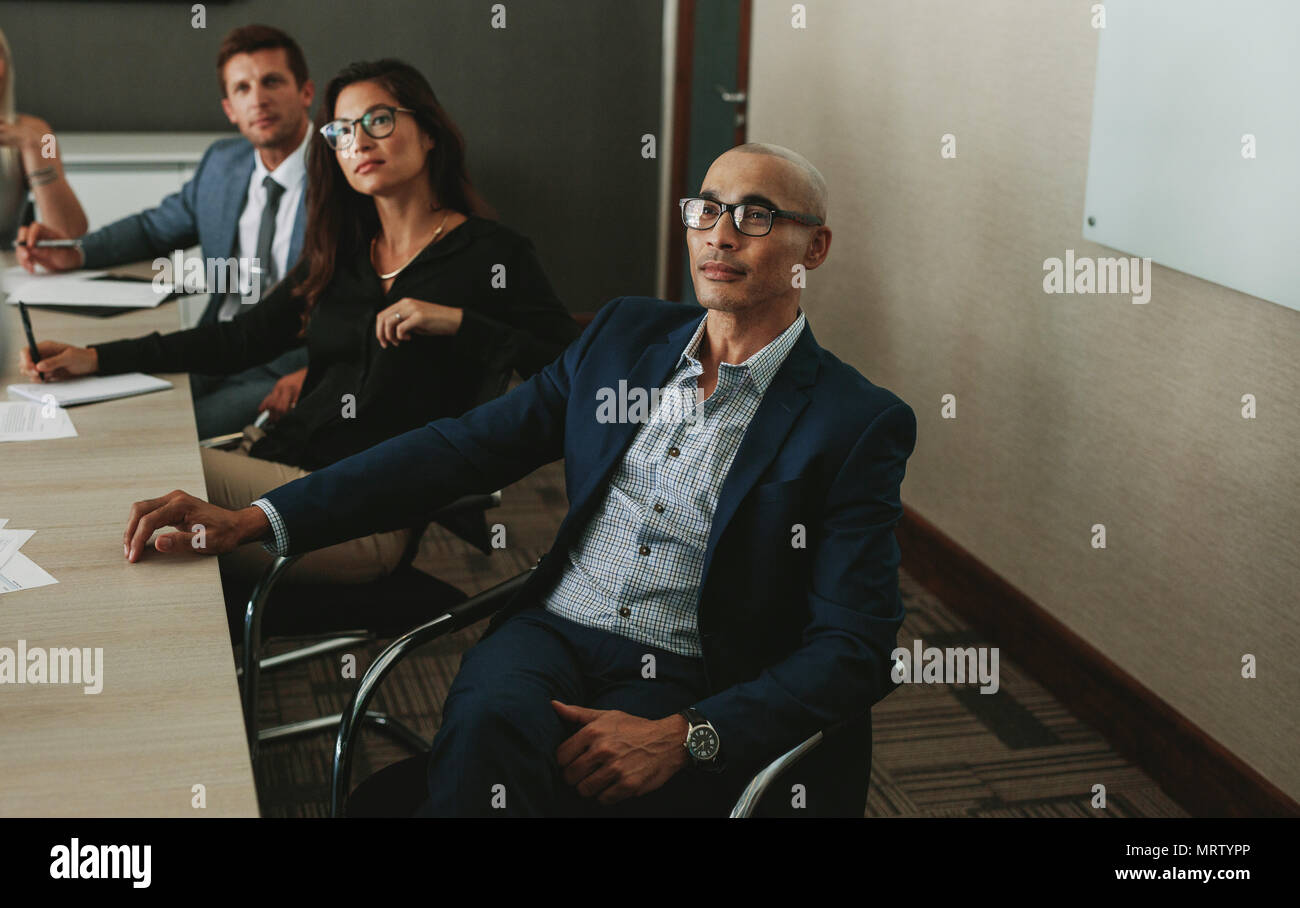Men and women sitting together and listening to a colleague's project discussion. Diverse business people sitting at conference table for corporate br - Stock Image