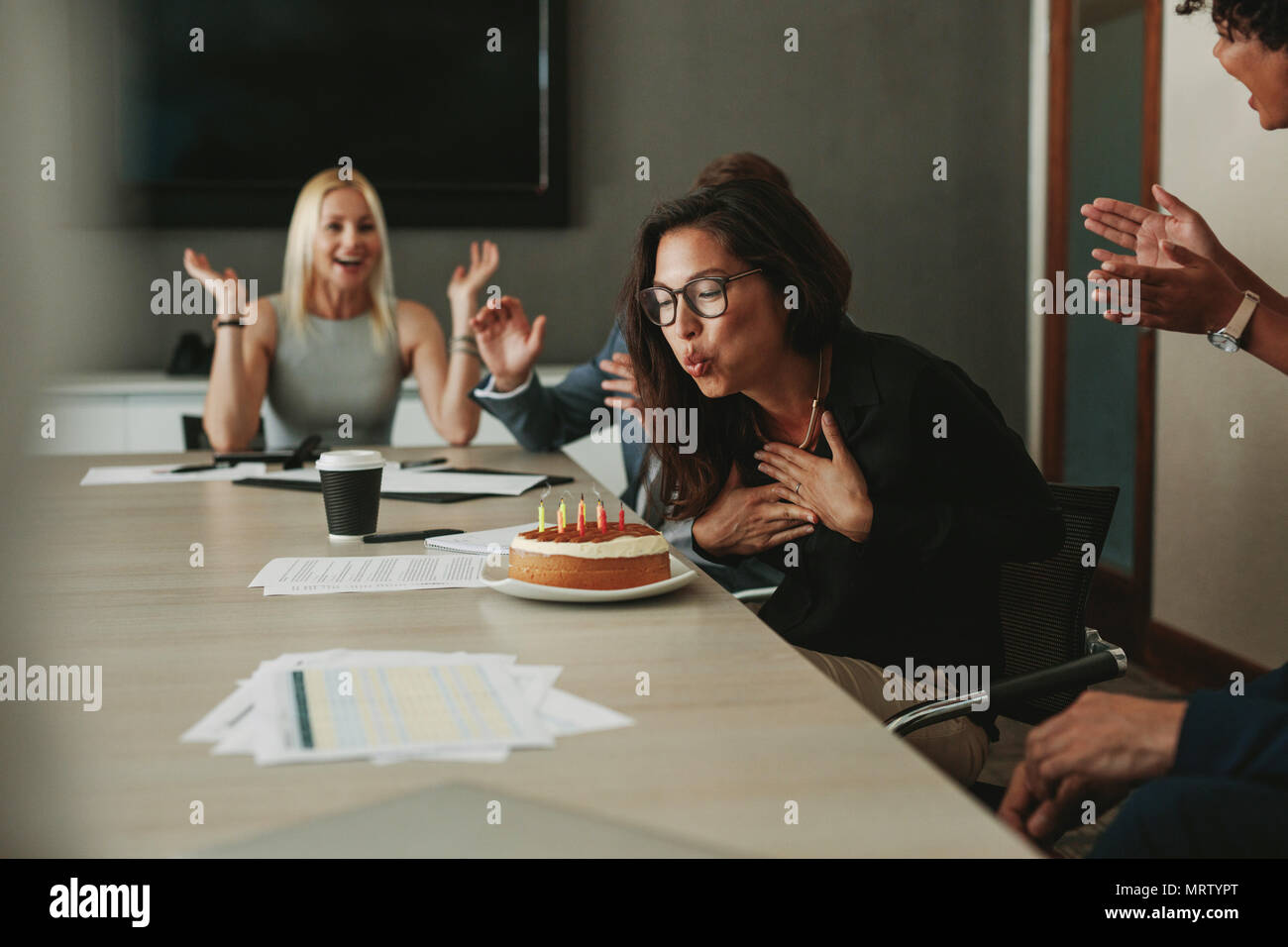 Businesswoman blowing candles on a birthday cake in the office. Asian female associate celebrating her birthday with colleagues in office. - Stock Image