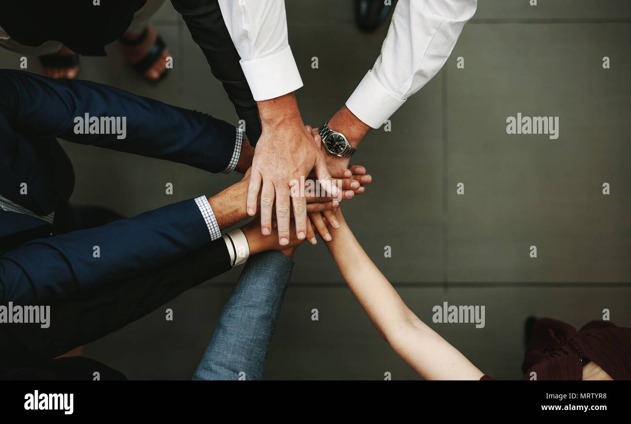 Unity and teamwork Concept. Top view of business people putting their hand together. - Stock Image