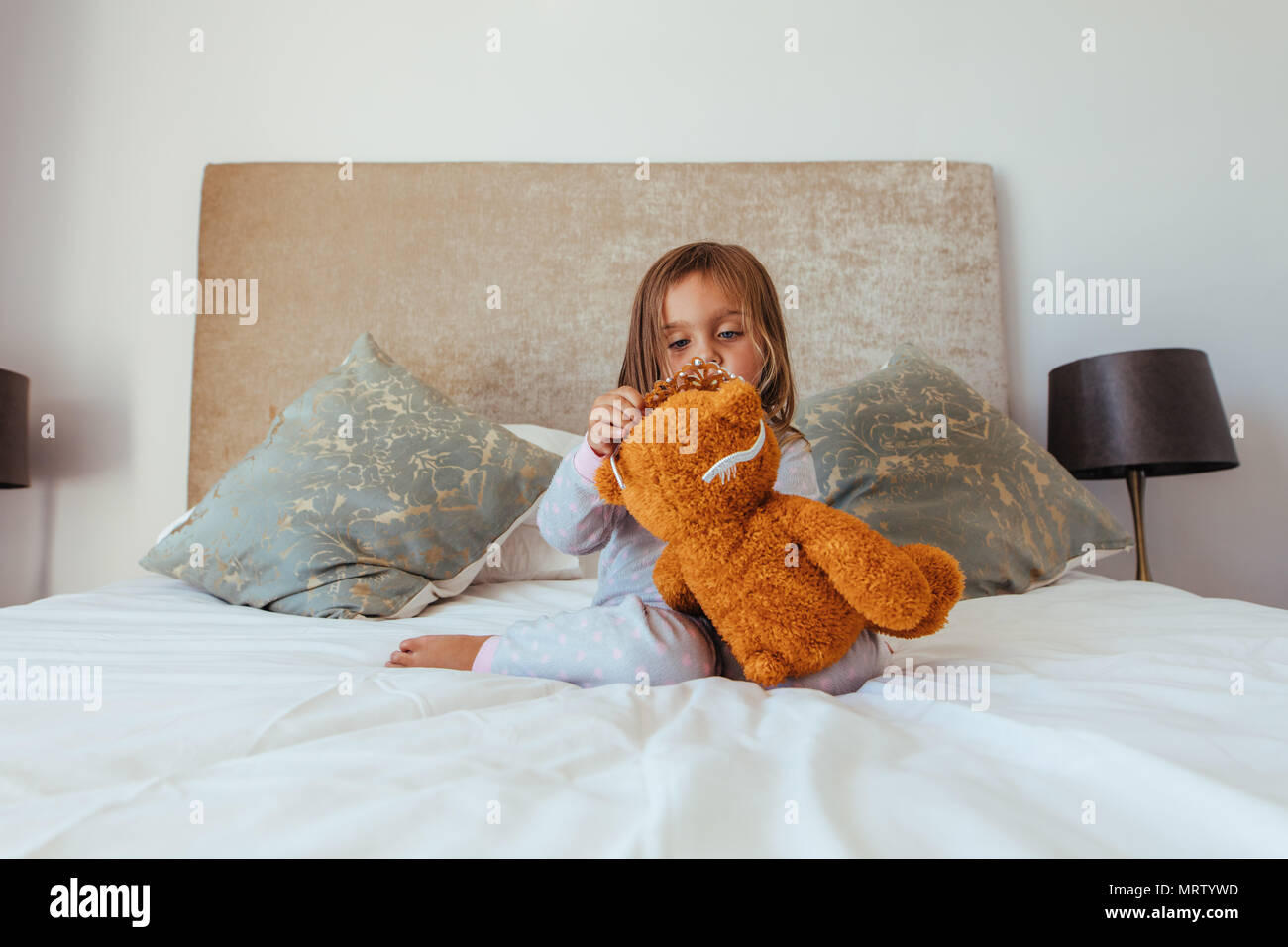 Cute little baby girl putting a crown on her teddy bear. Innocent girl child playing with her soft toy. - Stock Image