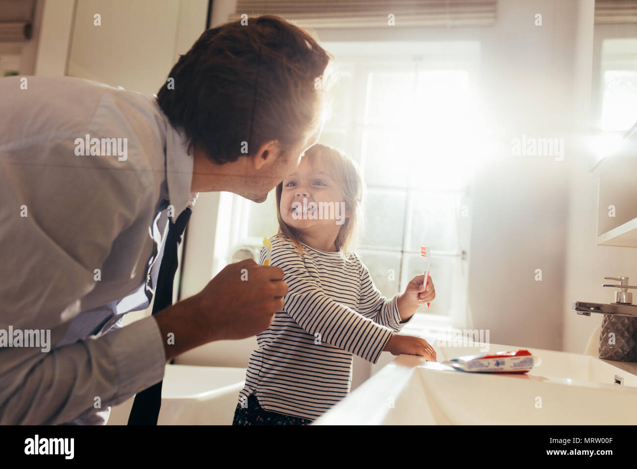 Father and daughter brushing teeth standing in bathroom and looking at each other. Man teaching his daughter how to brush teeth. - Stock Image