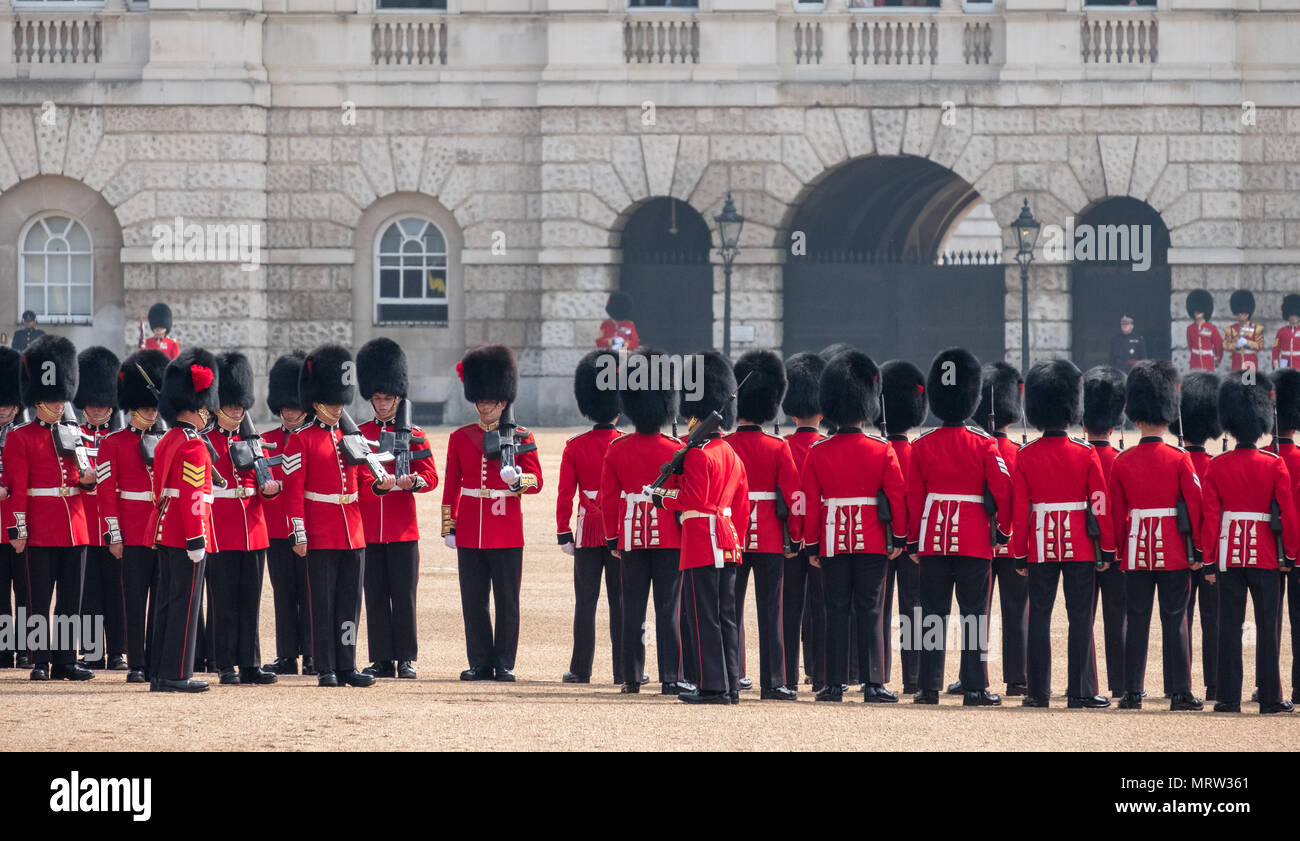 Trooping the Colour military ceremony in London UK, with Coldstream Guards lined up in their red and black traditional uniform and bearskin hats - Stock Image