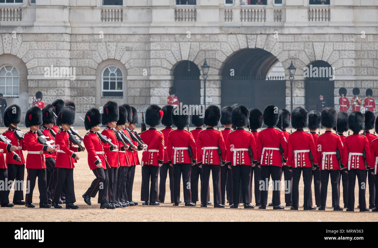 Trooping the Colour military ceremony in London UK, with Queen's Coldstream Guards lined up in red and black traditional uniform and bearskin hats - Stock Image