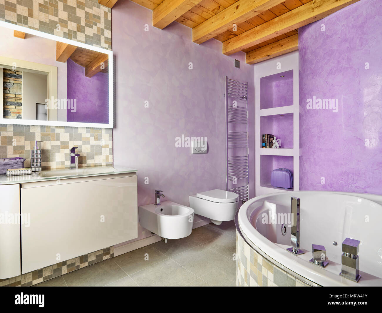 modern bathroom interior in the foreground the angular bathtub and to left a wooden furniture with a built-in washbasin on the background the niches,  - Stock Image
