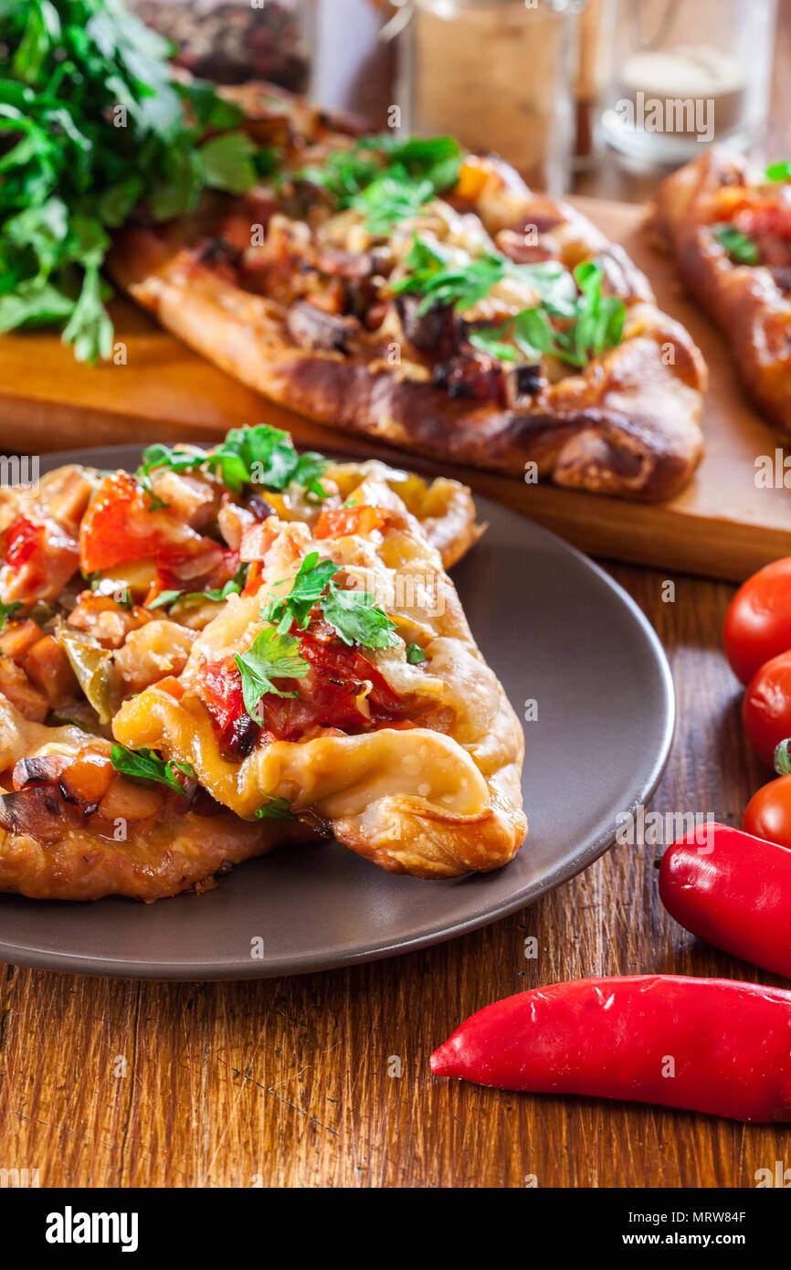 e51a30cc7bb54c Sliced traditional Turkish pide with meat and vegetables on a plate ...