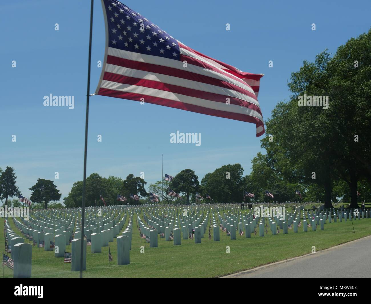 A big United States flag at half staff and small US flags wave in the wind at the Fort Gibson National Cemetery in Muskogee, Oklahoma Stock Photo