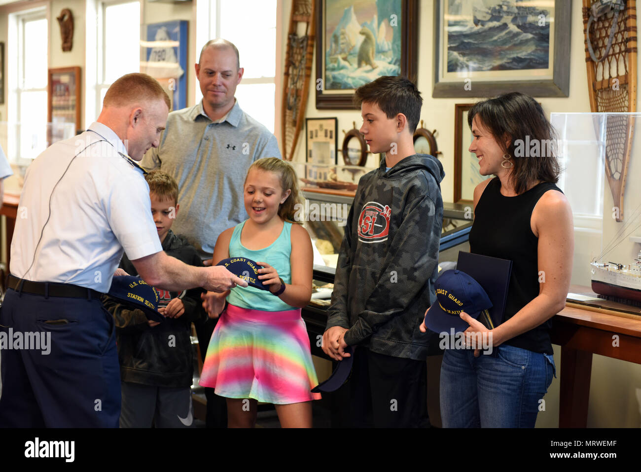 Rear Adm. David Throop, commander, Coast Guard 13th District, presents Darci Dawson and her family members with Coast Guard Station Seattle hats after giving Dawson the Meritorious Public Service Award at Base Seattle, July 7, 2017. Dawson was recognized for her selfless actions after she saved the life of a drowning toddler, Kaden Sluggett, on July 9, 2016, while on vacation in Montana. U.S. Coast Guard photo by Petty Officer 2nd Class Ali Flockerzi. - Stock Image