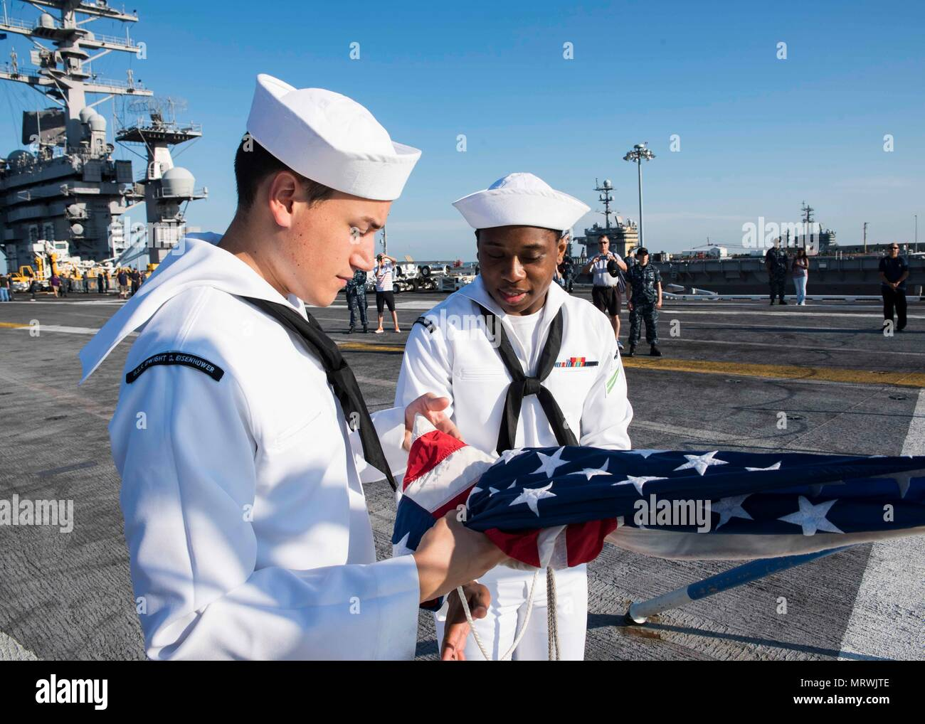 170708-N-KJ380-043   NORFOLK, Va. (July 8, 2017) Culinary Specialist 3rd Class Jose Maldonado, front, and Airman Terrance Nelson prepare to raise the ensign on the flight deck of the aircraft carrier USS Dwight D. Eisenhower (CVN 69)(Ike) during a friends and family day cruise. Ike is pier side during the sustainment phase of the Optimized Fleet Response Plan (OFRP). (U.S. Navy photo by Mass Communication Specialist Seaman Neo Greene III) - Stock Image