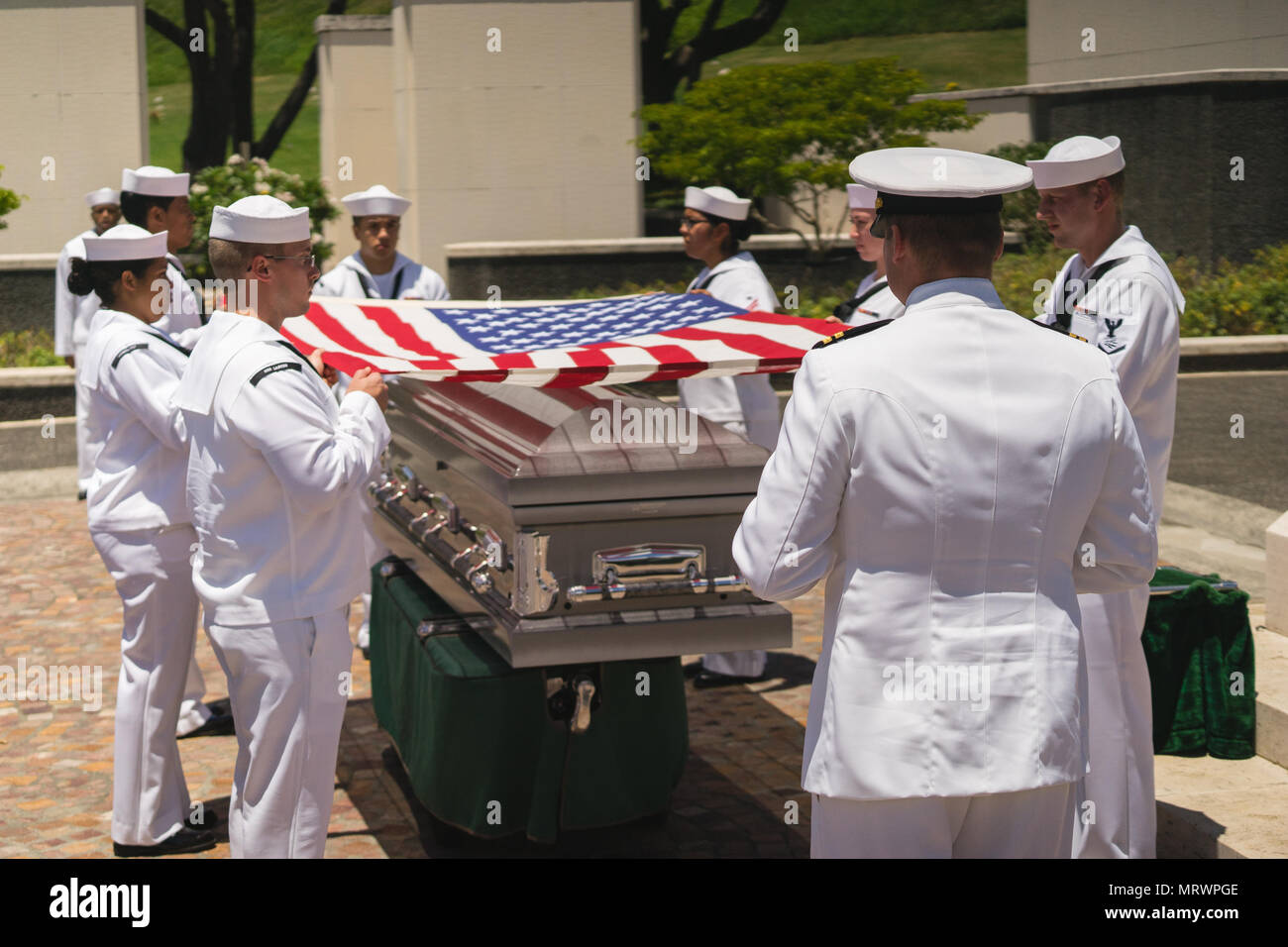 U.S. Navy Sailors drape the American flag over the casket. of U.S. Navy Seaman 1st Class Paul S. Raimond, of Converse, Louisiana, was laid to rest July 11, 2017 in the National Memorial Cemetery of the Pacific, in Honolulu, Hawaii. On Dec. 7, 1941, Raimond was assigned to the USS Oklahoma (BB-37), which was moored at Ford Island, Pearl Harbor, when the ship was attacked by Japanese aircraft. The attack on the ship resulted in the deaths of 429 crewmen, including Raimond. Raimond was recently identified through DNA analysis and returned to his family for burial with full military honors. (U.S.  - Stock Image