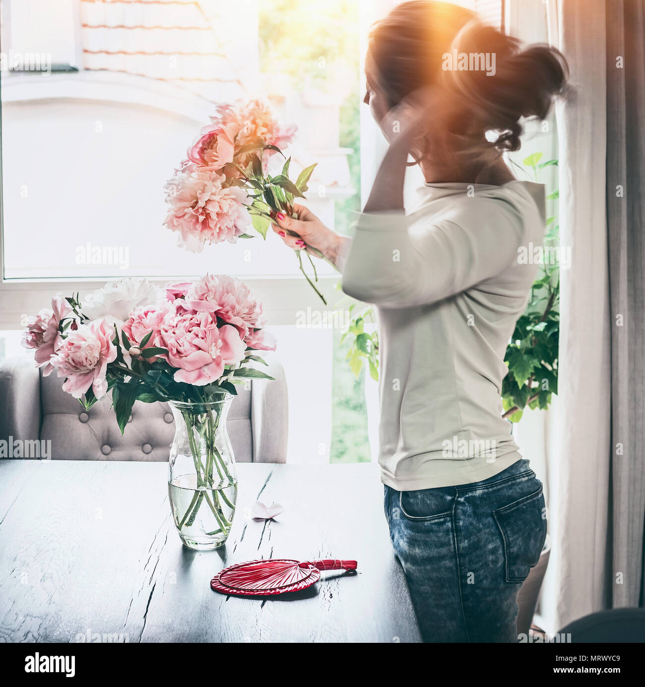 Shapely women arranging peonies bunch in glass vase on table at window with sunset light in living room. Lifestyle. Happy home Stock Photo