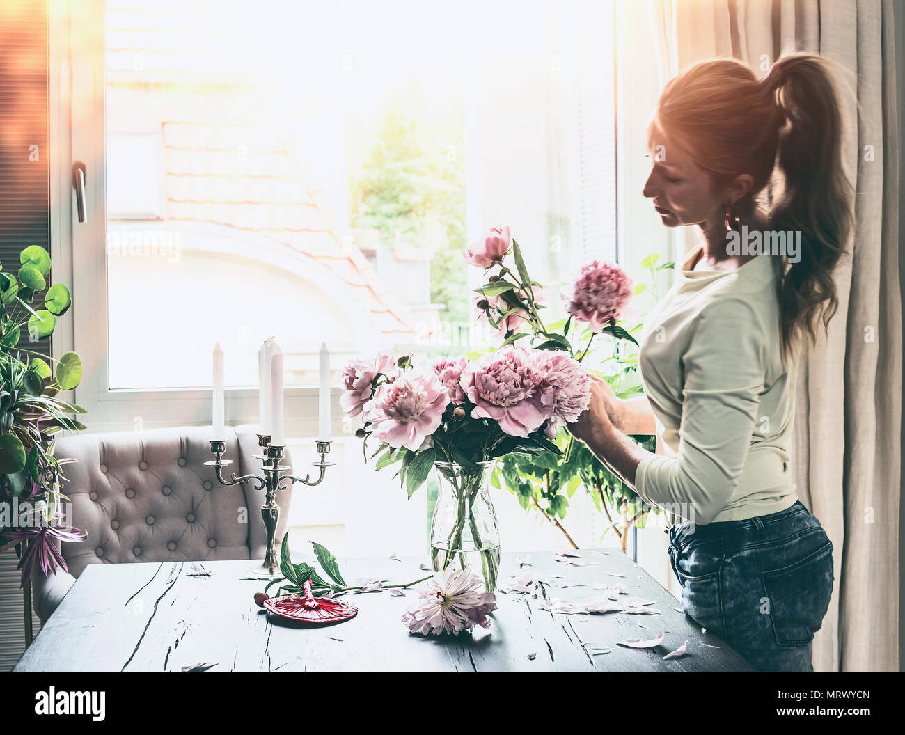 Beautiful modern women with pony tail hair arranging peonies bunch in glass  vase on table at window in living room. Lifestyle. Happy home 226095639d