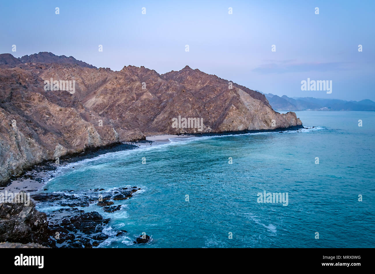 Beautiful bird's eye view of barren, pointy mountains and turquoise sea water in Oman. - Stock Image