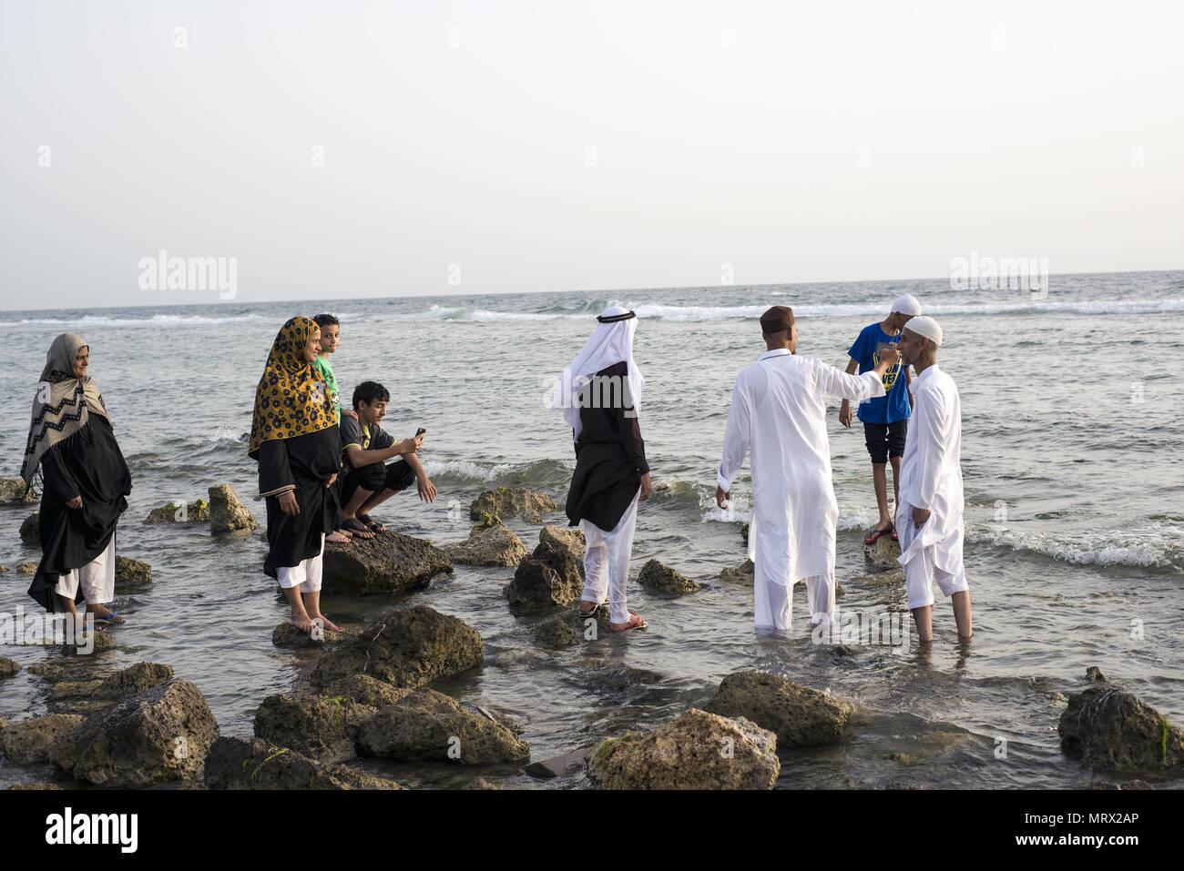 Pilgrims walking on rocks in the Red Sea during Ramadan in Jeddah, Saudi Arabia - Stock Image