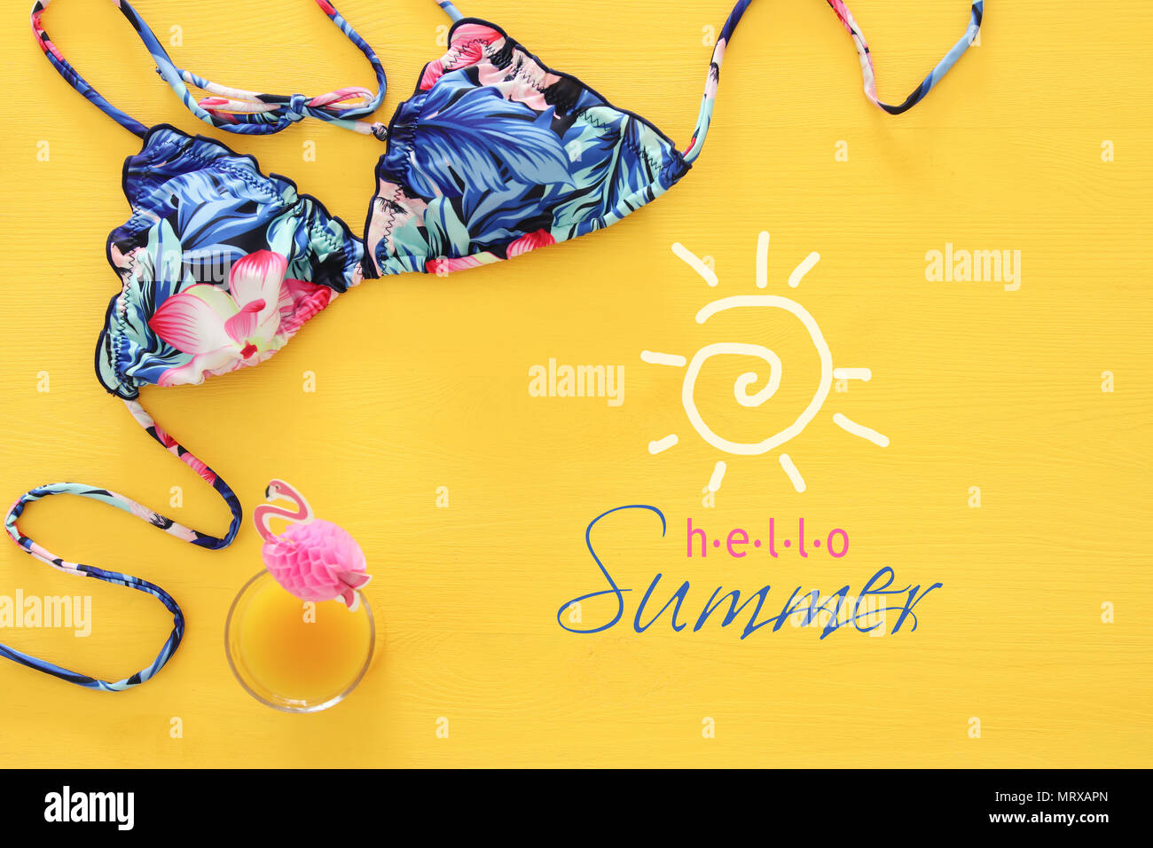 ef70818230 Top view of fashion female swimsuit bikini on yellow wooden background.  Summer beach vacation concept