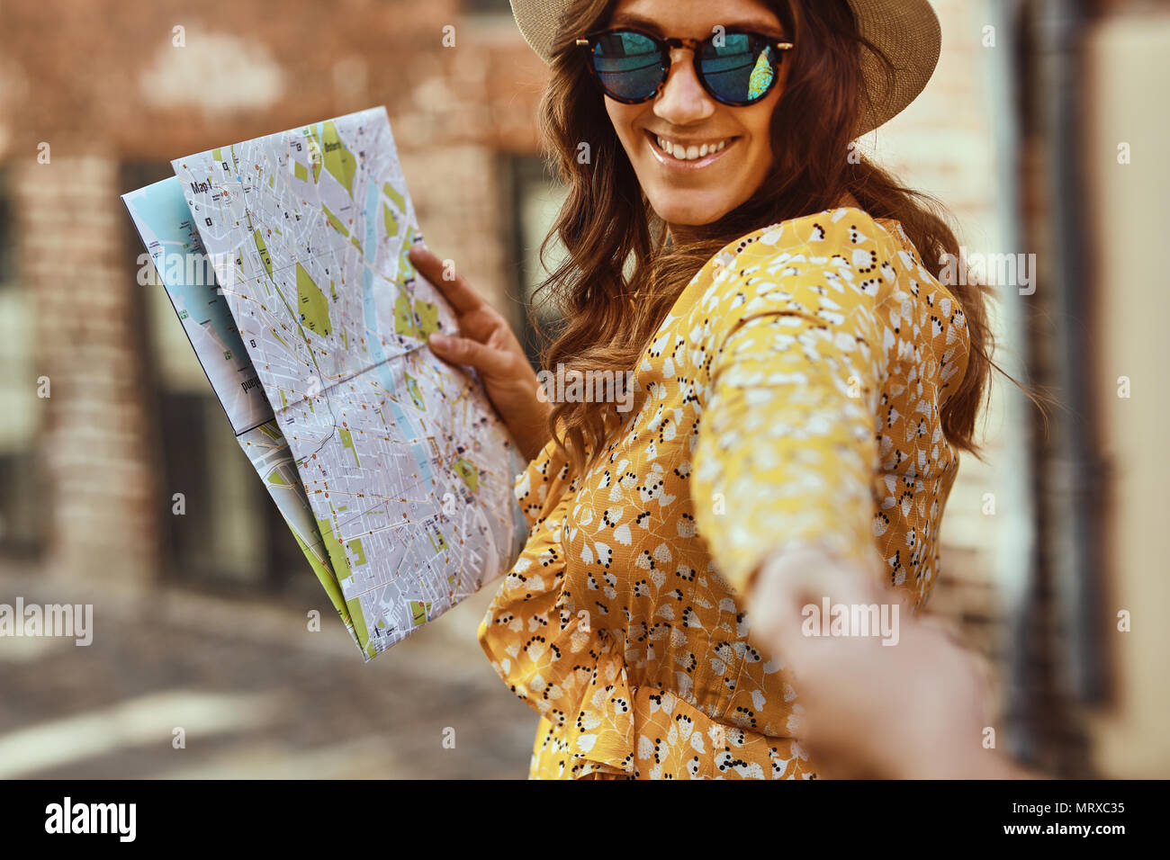 POV of a smiling young woman wearing sunglasses and holding a map leading another person by the hand while exploring a city together - Stock Image